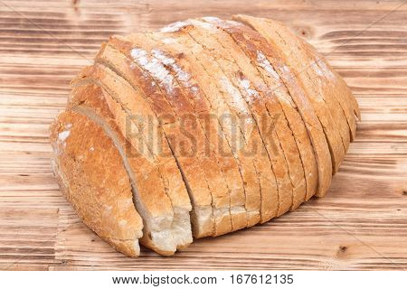 Sliced crusty country style round organic french bread isolated on wooden vintage tray
