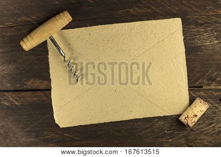 Photo of an old-fashioned corkscrew with a cork, shot from above on a dark brown background texture with a piece of old parchment for copyspace. Design template for a wine list or a tasting invitation