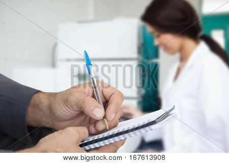 Close up of man writing in spiral book against cute scientist using a centrifuge Cute scientist using a centrifuge in a laboratory