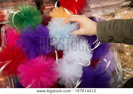 Hand holding a pompom among set of different colours a pompoms