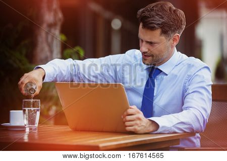 Handsome businessman pouring water in glass while using laptop at sidewalk cafe