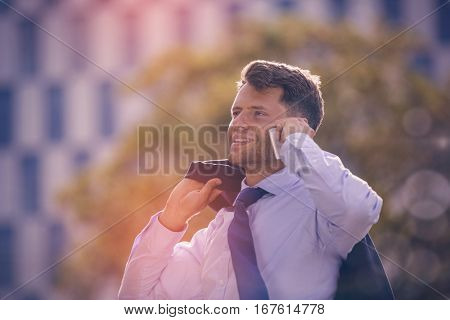 Smiling businessman holding blazer while talking on mobile phone