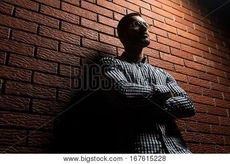 Man With Glasses Standing On Wall Of Bricks