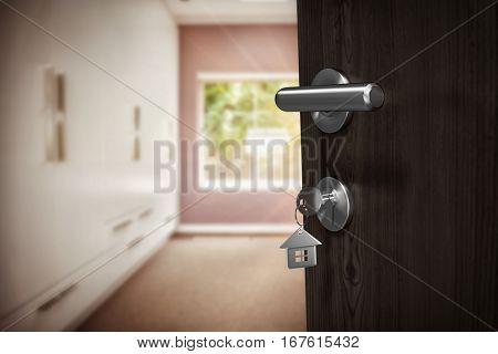 Digitally generated image of brown door with house key against walk in wardrobe in bedroom