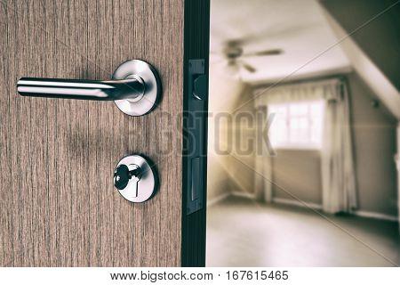 Brown door with doorknob and key against empty master bedroom in cream and beige