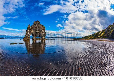 The concept of extreme northern tourism. The famous rock Hvitserkur -  huge mammoth. The north coast of Iceland. Ocean tide at sunset
