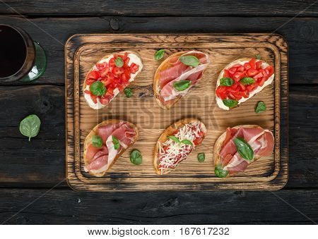 Set of small sandwiches with prosciutto tomatoes parmesan cheese fresh basil served on wooden board with glass of wine top view