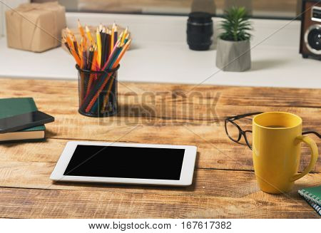 Home workplace with tablet coffee cup notepad and pencil.