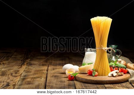 Raw Italian spaghetti with ingredients for cooking Italian pasta on wooden table with copy space