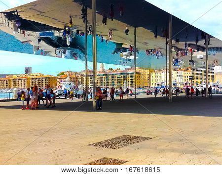 Marseille France - September 08 2015: Tourists walking under reflecting awning made of polished steel by British architect Lord Norman Foster at Old port of Marseille France on September 08 2015