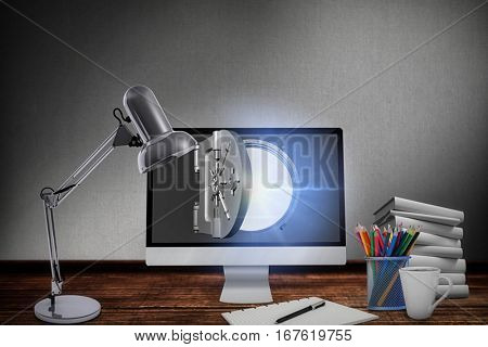 Table lamp by computer and books against digitally generated grey background