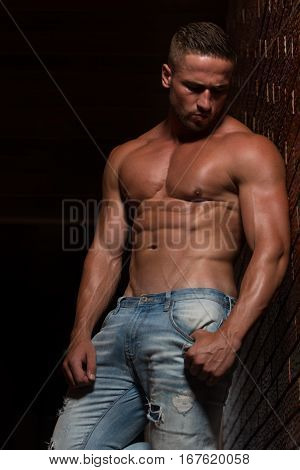 Man Flexing Muscles On Wall Of Bricks