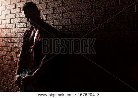 Bodybuilder Flexing Muscles On Wall Of Bricks