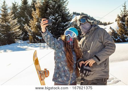 ?ouple snowboarder standing on a mountain top at sunset and making a selfie. Mountains in the background