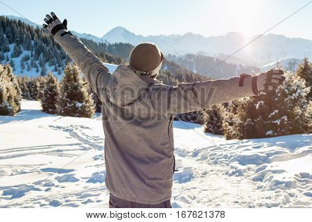 Snowboarder stands mountain top with his arms raised at sunset. Mountains in the background