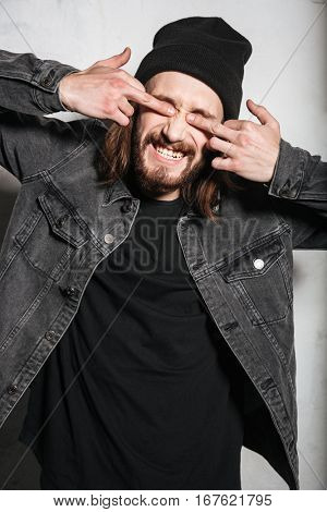 Portrait of a smiling hipster man showing fuck you sign and covering eyes with fingers isolated over wall background