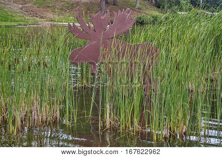 Wooden moose standing in the bulrushes in a lake