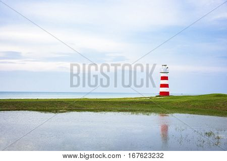 Lighthouse On Greensward And Sky Blue Near Sea
