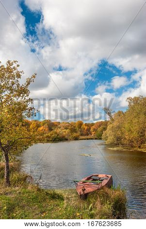 Beautiful autumn landscape with old boat on the riverbank against a forest