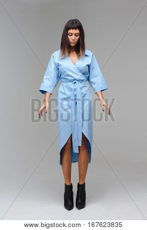 Young beautifeul woman looking down in studio with grey background. She wears a blue cloak and black boots. She behaves herself like she is standing on the brink