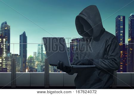 Hooded Hacker With Vendetta Mask Stealing Information With Laptop