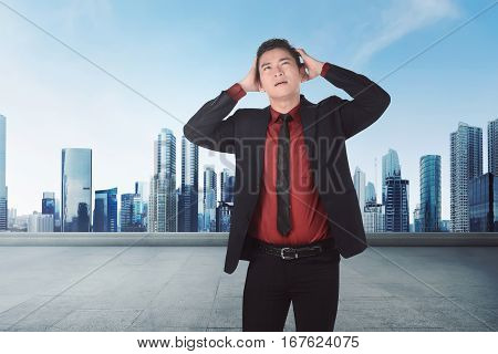 Young Asian Businessman Suffering From Headache