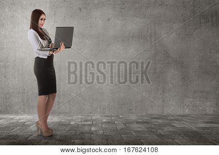 Smiling Asian Business Woman Typing While Holding Laptop