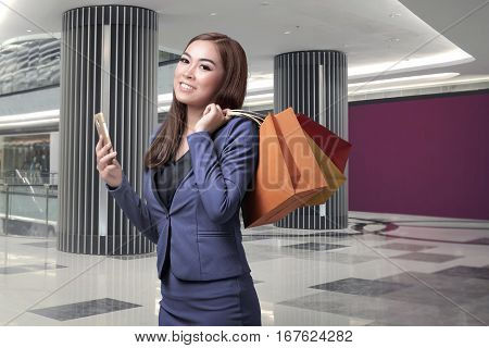 Young Asian Business Woman With Shopping Bags Holding Mobile Phone