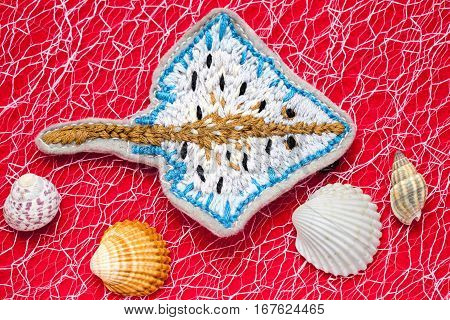 hand embroidered ramp on a red background among seashells
