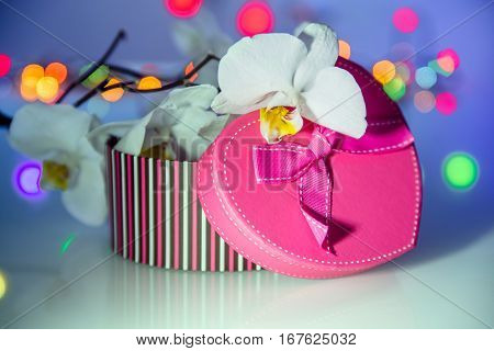 Pink gift box in form of heart on the background of the white orchid