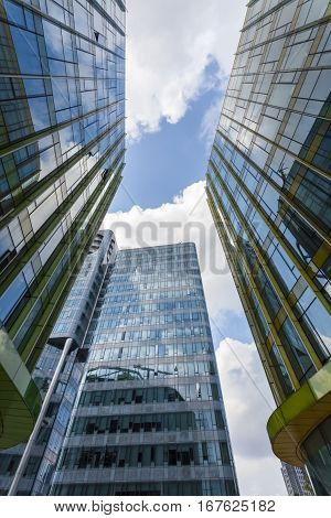 upward view of modern glass buildings with blue sky