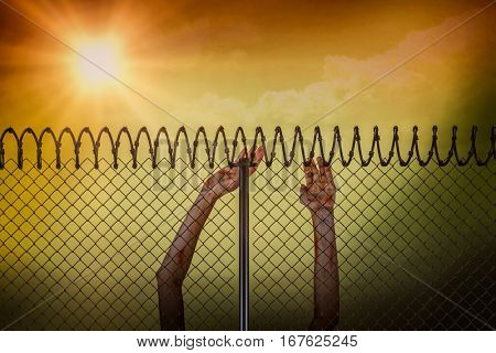 Blond woman standing with eyes closed and arms up against chainlink fence by white background