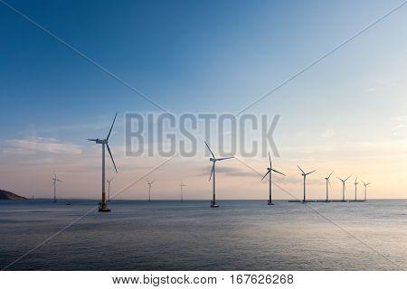 offshore wind farm at dusk renewable energy background