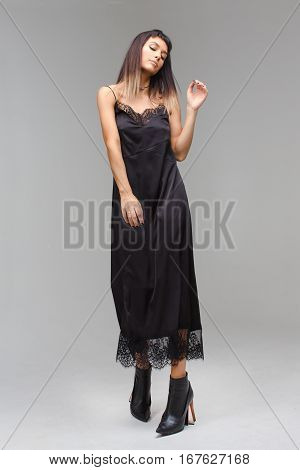 Beutiful model in grey background studio playfully looks down. She is wearing nightie and her hand is up.