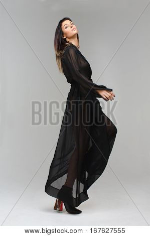 Nice model in diaphanous nightie playfully looking to the photograther camera making a step in studio with grey background. Her nightie is black, her figure is perfect