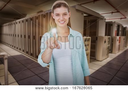 Pretty hipster pointing with her finger against data center