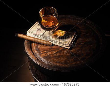 Cognac ,cigar And Dollars On Old Oak Barrel