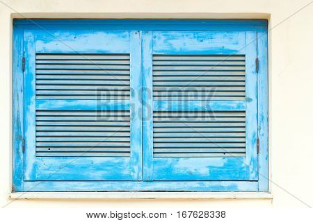 Blue wooden window shutters with vents in white stone wall. Classic resort Greek architecture white-blue building of house on shore of Cretan sea. Resort village Bali Rethymno
