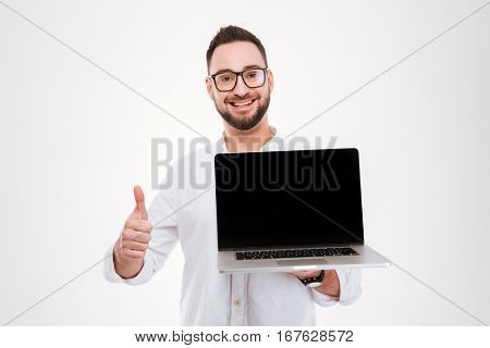 Image of happy attractive young bearded man dressed in white shirt wearing glasses holding laptop and showing display to camera while make thimbs up gesture isolated over white background.