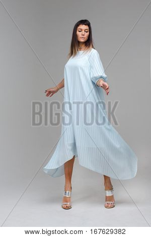 Nice woman pretending like she is flying in studio with grey background. She is wearing long white nighty whith is flutterring