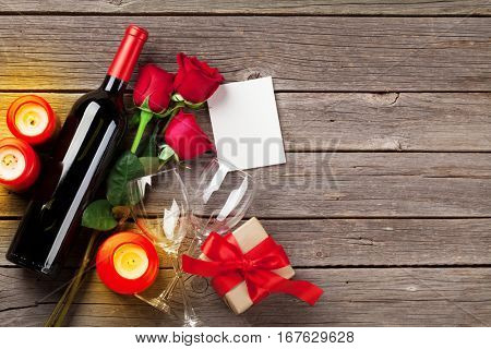 Valentines day greeting card, red rose flowers, wine and gift box on wooden table. Top view with copy space