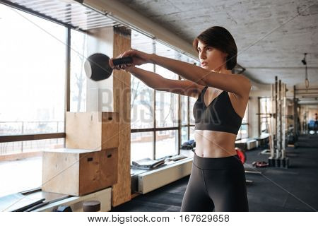 Concentrated young fitness woman doing exercices with kettleball in gym