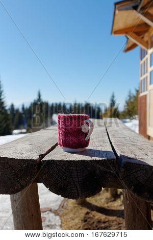 Tea Mug On Wooden Picnic Table During Winter. Knitted Mug Cozy.