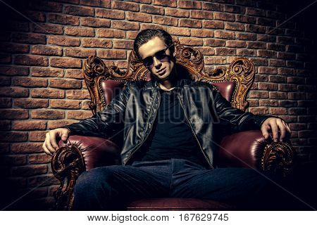 Portrait of a brutal confident young man sitting relaxed in expensive vintage armchair. Mafia, criminal concept.