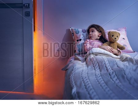Nightmare for children. Little child girl is afraid of monsters in the dark of night.