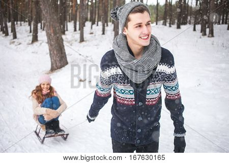Young couple walking and sledding in the winter in the forest during a snowfall