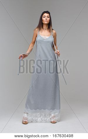 Nice prideful model wearing long grey lace nighty standing in studio with grey background looking to the photograther with open hands