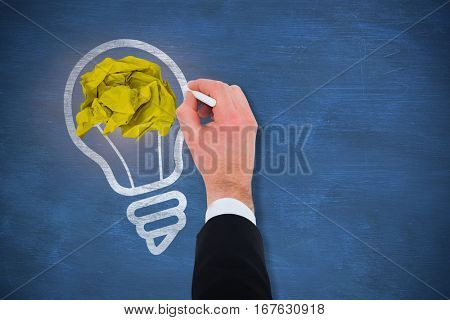 Hand of businessman writing with a white chalk against blue chalkboard