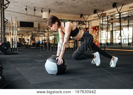 Serious young sportswoman working out with ball in gym
