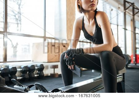 Attractive young sportswoman sitting and working out in gym